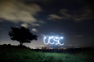 Photo by Matthew Forman of letters UCSC written in light at nighttime overlooking campus