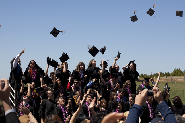 Graduates celebrate commencement by throwing their caps in the air