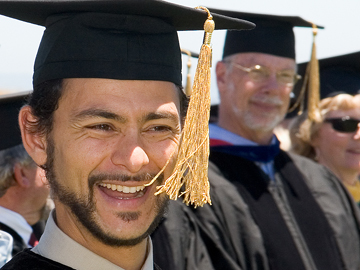 Smiling student in cap and gown at graduation ceremony